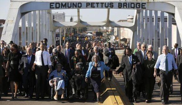 Obama participates in a march across the Edmund Pettus Bridge in Selma, Alabama
